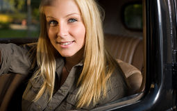 Beautiful young blond girl in a vintage car. Beautiful young blond girl smiling in a black vintage car, looking at the camera royalty free stock images