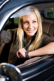 Beautiful young blond girl in a vintage car. Beautiful young blond girl smiling in a black vintage car, looking at the camera stock images