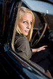 Beautiful young blond girl in a vintage car. Portrait of a beautiful young blond in a vintage car, shot through the door window stock photography