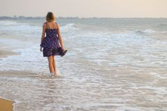 Beautiful young blond girl walking on beach Royalty Free Stock Photos
