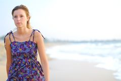 Beautiful young blond girl walking on beach Royalty Free Stock Images