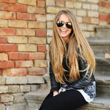 Beautiful young blond hair woman sitting on stairs and smiling w Royalty Free Stock Photo
