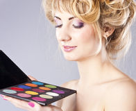 Beautiful young blond, holding eye shadow palette Royalty Free Stock Photo