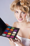 Beautiful young blond, holding eye shadow palette Stock Images