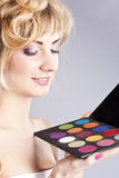 Beautiful young blond, holding eye shadow palette Stock Image