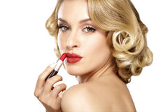 Beautiful young blond model curly hair applying lipstick Stock Photo