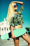 Beautiful young blond model girl in summer hipster clothes with skateboard Royalty Free Stock Photo