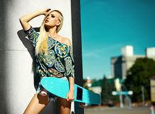 Beautiful young blond model girl in summer hipster clothes with skateboard Royalty Free Stock Photography