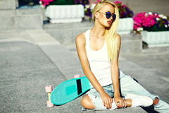 Beautiful young blond model girl in summer hipster clothes with skateboard Stock Photo