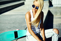 Beautiful young blond model girl in summer hipster clothes with skateboard Royalty Free Stock Image