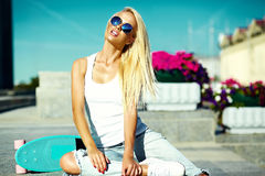 Beautiful young blond model girl in summer hipster clothes with skateboard Stock Image