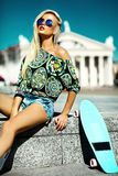 Beautiful young blond model girl in summer hipster clothes with skateboard Stock Images