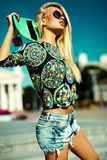 Beautiful young blond model girl in summer hipster clothes with skateboard Royalty Free Stock Images
