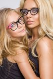 Beautiful blonde female model, mother with blonde daughter hug. Beautiful young blond mom of an adorable little baby girl with long hair in black glasses royalty free stock photography