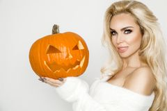 Beautiful young woman in white sweater, standing on white background and holding pumpkin;. Beautiful young blond sexy woman model in white sweater, standing on Stock Photography