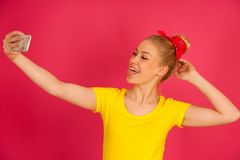 Beautiful young blond teenage woman in yellow t shirt  taking se. Lfie over pink background Royalty Free Stock Image