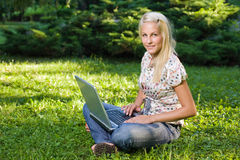 Beautiful young blond using laptop outdoors. Royalty Free Stock Photography