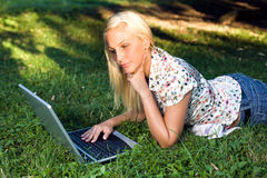 Beautiful young blond using laptop outdoors. Royalty Free Stock Images