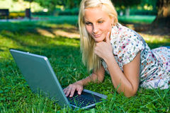 Beautiful young blond using laptop outdoors. Stock Photo