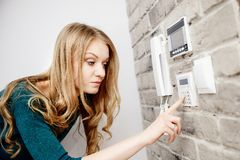 Beautiful young blond woman activates an alarm in the house Royalty Free Stock Photos
