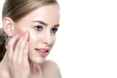 Beautiful Young Blond Woman applying Face cream under her eyes. Facial treatment. Cosmetology, beauty and spa concept. Isolated on white background royalty free stock photography