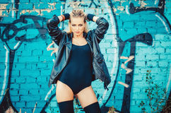 Beautiful young blond woman in a black body in leather jacket standing on the background of painted wall on the street Royalty Free Stock Image