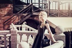 Beautiful young blond woman in a black dress Royalty Free Stock Images