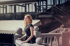 Beautiful young blond woman in a black dress Royalty Free Stock Photography