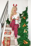 A beautiful young blond woman in Christmas pajamas and with reindeer horns, sitting on the steps, decorated with fir branches and royalty free stock photos