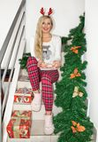 Beautiful young blond woman in Christmas pajamas and with reindeer horns, sitting on the steps and holding a cookie decorated stock image
