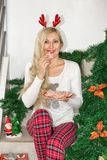 Beautiful young blond woman in Christmas pajamas and with reindeer horns, sitting on the steps and holding a cookie decorated stock images