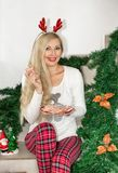 Beautiful young blond woman in Christmas pajamas and with reindeer horns, sitting on the steps and holding a cookie decorated stock photography