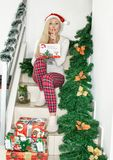 A beautiful young blond woman in Christmas pajamas and with a Santa hat sitting on the steps, decorated with fir branches and gift royalty free stock image
