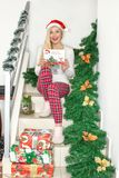 A beautiful young blond woman in Christmas pajamas and with a Santa hat sitting on the steps, decorated with fir branches and gift stock image