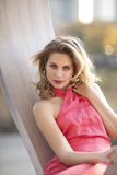 A beautiful young blond woman with a coral halter dress sitting in structure near Lincoln Park Zoo. A beautiful young blond woman with a coral halter dress Stock Photos