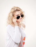 Beautiful young blond woman in dark glasses and white sweater. Beautiful young blond woman in dark glasses and a white sweater Royalty Free Stock Images