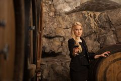 Beautiful young blond woman drinks wine in wine cellar Stock Image