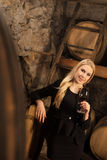 Beautiful young blond woman drinks wine in wine cellar Stock Photography