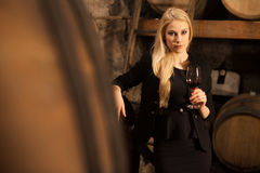 Beautiful young blond woman drinks wine in wine cellar Stock Photo