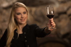Beautiful young blond woman drinks wine in wine cellar Stock Images
