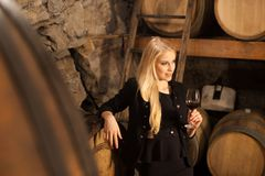 Beautiful young blond woman drinks wine in wine cellar.  Royalty Free Stock Images