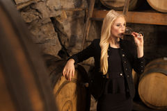 Beautiful young blond woman drinks wine in wine cellar.  Stock Image