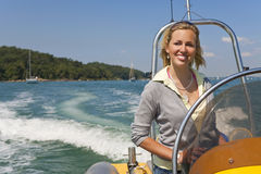 Beautiful Young Blond Woman Driving A Speedboat royalty free stock image