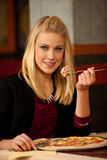 Beautiful young blond woman eating pizza in restaurant. Beautiful blond woman eating pizza in restaurant royalty free stock photos