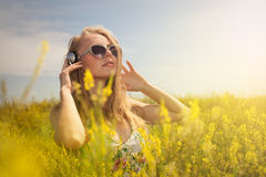 Beautiful young  blond woman with headphones outdoors enjoying m Stock Images