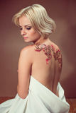 Beautiful young blond woman. Beautiful blond woman with henna tattoo on her back Royalty Free Stock Images