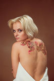 Beautiful young blond woman. Beautiful blond woman with henna tattoo on her back Stock Photography