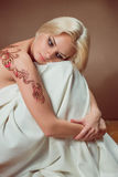 Beautiful young blond woman. Beautiful blond woman with henna tattoo on her back Royalty Free Stock Photography