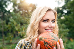 Beautiful young blond woman in her garden harvesting pumpkins Stock Photos