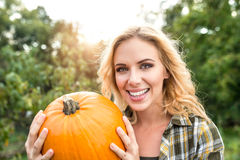 Beautiful young blond woman in her garden harvesting pumpkins Stock Image